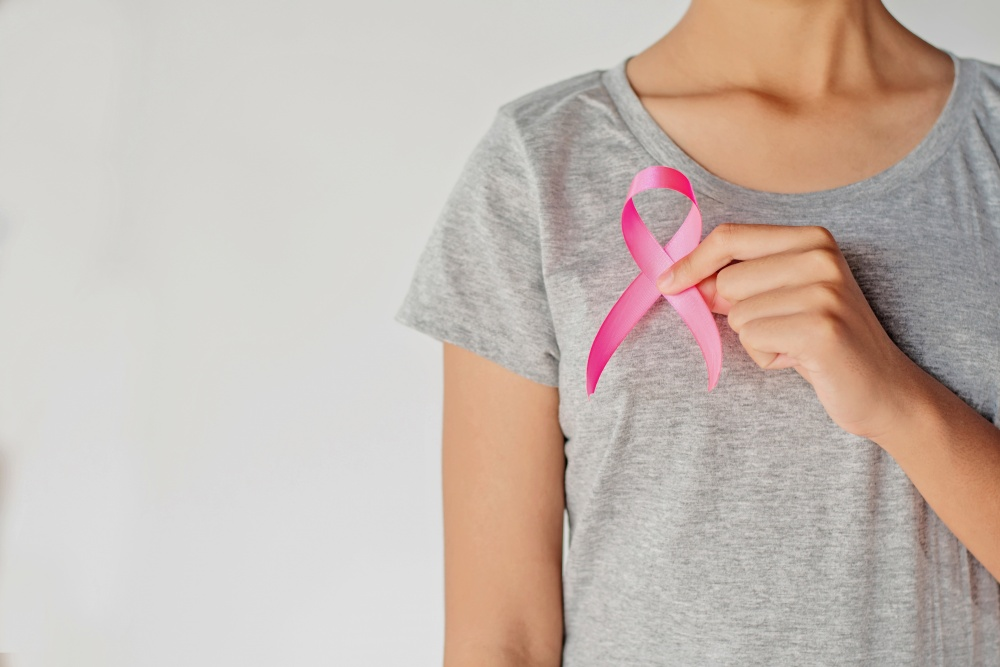 Woman in grey shirt holding breast cancer ribbon to chest